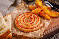 Spiral sausage grilled. with golden crispy delicious french fries. Fast food in the restaurant. Delicious fried spiral Royalty Free Stock Photography