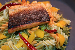 Spiral shaped pasta with garlic, dried red chili, yellow pepper and olive oil topped with grilled Salmon Stock Images