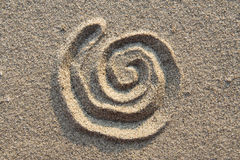 Spiral sign in sand. Spiral sign on sand. Sign on sand beach closeup Stock Photos