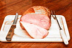 Spiral Sliced Ham on Cutting Board with Utensils Royalty Free Stock Images