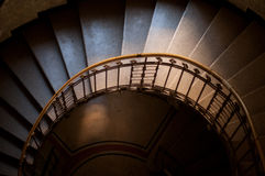 Spiral staircase. Looking down the center of an old stone spiral staircase with a tiled floor in shadow below stock images