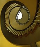 Spiral Staircase. A wooden spiral staircase twists and rises toward the light royalty free stock photos