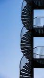 Spiral staircase against a blue sky. Black spiral staircase against a blue sky Royalty Free Stock Photos