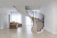Spiral staircase in bright interior with white brick wall in elite expensive stock photos