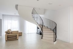 Spiral staircase in bright interior with white brick wall in elite expensive apartment stock photography