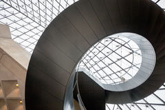 Spiral staircase and glass pyramid at The Louvre Royalty Free Stock Photo