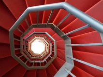 Spiral staircase of iron. Covered with a red carpet Stock Photo