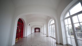 Spiral staircase and long white corridor with doors