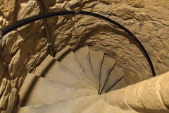 Spiral staircase. A narrow spiral staircase of stone in an underground structure. Can be used as metaphor for something spiraling out of control stock images