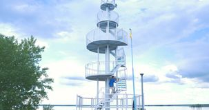Spiral staircase near the late. A young man rises to a Spiral staircase near the lake stock footage