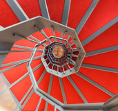 Spiral staircase with red carpet in a building Stock Photos