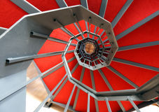 Spiral staircase with red carpet in a modern building Stock Images