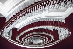 Spiral staircase in red and white. Architectural symmetry with elegant spiral stairways, above view, made of white marble and covered with red carpet, in a hotel royalty free stock photography