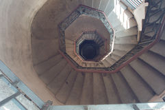 Spiral staircase with stone steps. And handrails brown royalty free stock images