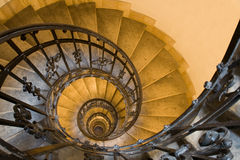 Spiral staircase and stone steps in old tower. Spiral staircase, forged handrail and stone steps in old tower Stock Photos