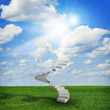 Spiral stairs in sky with green grass, clouds and Stock Image