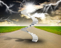 Spiral stairs in sky with green grass, road and Royalty Free Stock Images