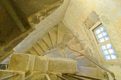 Spiral stone stairs in an old castle seen from above. A birds eye side lit view of an ancient stone spiral staircase in oxford prison, oxford, uk.  The castle Stock Images