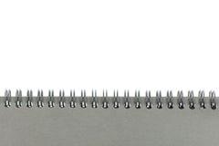 Spiral tråd som är destinerad eller - den destinerade sketchbooken som gjordes från grå färgbräde, isolerade vit bakgrund Royaltyfria Bilder