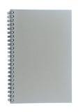 Spiral tråd som är destinerad eller - destinerad sketchbook som göras från det isolerade grå färgbrädet på vit bakgrund Royaltyfri Fotografi