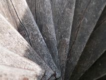 Spiral wooden staircase going down. Old spiral wooden staircase with dirt and cracks going down royalty free stock photography