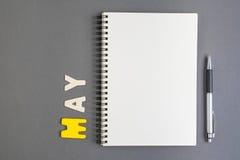 Spirala otwarty notatnik z pióra i Maja miesiąca sformułowaniami obrazy royalty free