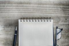 Spiralanteckningsbok för vit fyrkant därefter med pennan och glasögon på tabellen Royaltyfri Foto