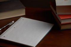 Spiralanteckningsbok på skrivbordet med böcker royaltyfri fotografi