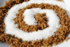 Spirale con zucchero bianco e marrone Fotografia Stock Libera da Diritti