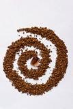 Spirale de café avec un cube en sucre de canne sur le blanc Photos libres de droits