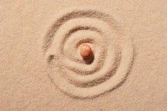 Spirale dessinée sur le sable de plage avec la pierre ronde rose de mer au centre Photographie stock libre de droits
