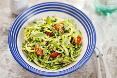 Spiralled courgette with green pesto and cherry tomatoes. Spiralled courgette spaghetti with green pesto and cherry tomatoes stock photo