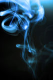 Spiralling Cigarette Smoke. An ascending spiral of blue smoke from a burning cigarette Royalty Free Stock Photo