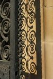 Spiraled wrought iron railing door with shadow. Spirals of curlicued metalwork cast a shadow on background of beige limestone wall royalty free stock photos