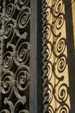 Spiraled wrought iron railing door with shadow. Spirals of curlicued metalwork cast a shadow on background of beige limestone wall royalty free stock image