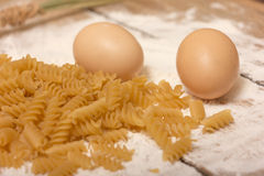 Spirals pasta. Eggs and wheat flour on wooden surface stock images