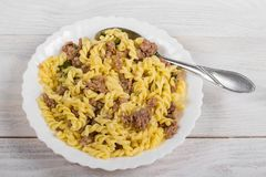 Spirals pasta with minced meat on a white plate on a wooden background. Italian food royalty free stock image