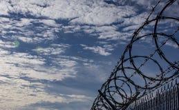 Spiralt taggtrådstaket med ljusa blå himmel och moln i Backgroud arkivfoto