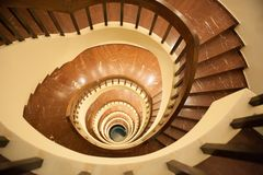 Spiraltrappuppgång, brant nedstigning ner trappan royaltyfria foton