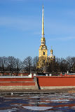 Spire of Cathedral against the sky. The spire of the main cathedral against the blue sky and the walls of the Petropavlovskaya fortress on the banks of the Neva stock image