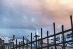 Spire of Catholic church with cross and wrought fence. Spire of the Catholic church with a cross on a background of cloudy sky. In the foreground lattice metal Stock Photography