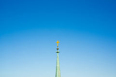 Spire with christian cross. On the top. Spire as metaphor of vertical worship heading up to god and heaven. Minimalistic copy space composition Stock Photography