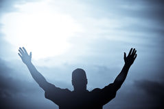 Spirit. A man proclaiming victory after reaching the end of his journey against a moonlit sky Royalty Free Stock Photo