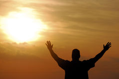Spirit. A man proclaiming victory after reaching the end of his journey against a sunset sky Royalty Free Stock Image