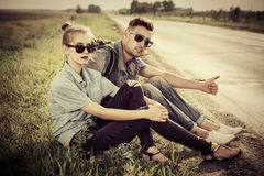 Spirit of adventure. Hitchhiking couple. Happy young people sitting by the highway Stock Photography