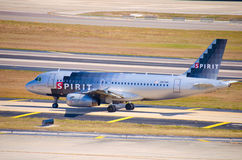 Spirit Airlines plane taxiing on airport tarmac. Full width photo of a Spirit Airlines jetliner taxiing on the tarmac after a landing royalty free stock image
