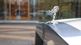 Spirit of Ecstacy or Emily logo on the hood of a rolls Royce. and bride the background. Emmy or Spirit of Ecstacy, hood royalty free stock photography