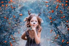 Spirit of the forest in the form of a child in a light brown dress, a baby deer playfully leads into the forest, the stock photos
