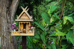 Spirit house in thailand. With flowers in vases and some wreathes Royalty Free Stock Images
