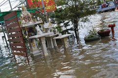 A spirit house is underwater in a flooded street of Pathum Thani in October 2011.  Stock Photos